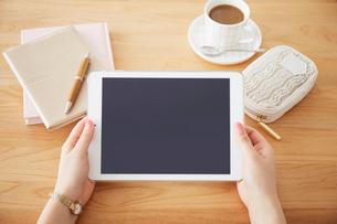 テーブルの上でタブレットを持つ女性の写真素材 [FYI02477337]