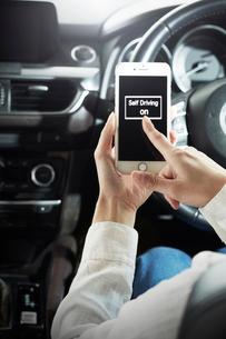 自動運転車でスマートフォンを操作する女性の写真素材 [FYI02477338]
