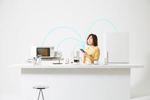 スマートフォンで家電を操作する女性の写真素材 [FYI02478826]