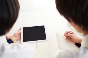 机の上でタブレットを利用して勉強する男女の高校生の写真素材 [FYI02478829]