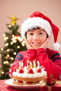 クリスマスでケーキとプレゼントを前に微笑む男の子の写真素材 [FYI02478935]