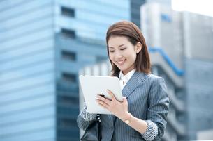 オフィス街に立ってタブレット型PCを持つ20代OLの写真素材 [FYI02479051]