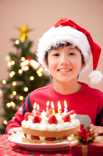 クリスマスでケーキとプレゼントを前に微笑む男の子の写真素材 [FYI02479075]