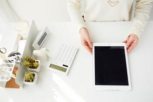白いテーブルの上でタブレット端末を持つ女性の写真素材 [FYI02479284]