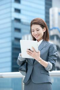 オフィス街に立ってタブレット型PCを持つ20代OLの写真素材 [FYI02479763]