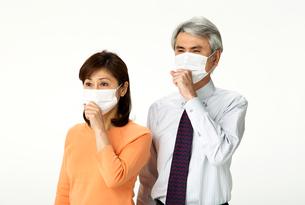 咳をしてマスクをする中年夫婦の写真素材 [FYI02481136]