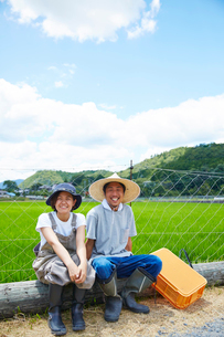 水田の前で丸太に腰掛ける笑顔の男女の写真素材 [FYI02481354]