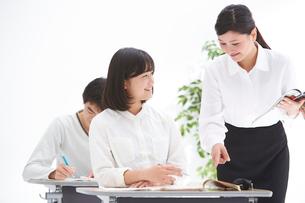 塾で授業中の高校生男女と女性教師の写真素材 [FYI02483246]