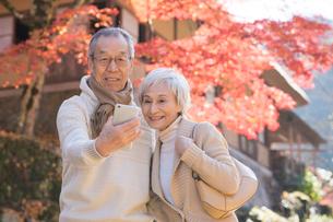 紅葉バックにカメラで撮影するシニア夫婦の写真素材 [FYI02483490]