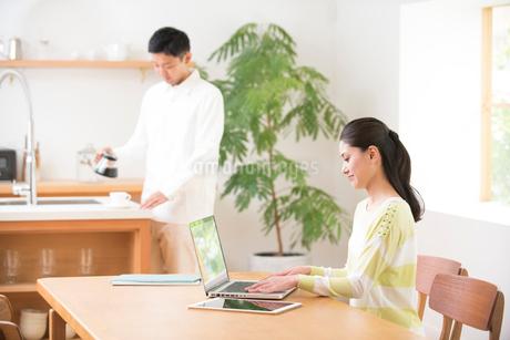 テレワーク中の女性にコーヒーを入れる男性の写真素材 [FYI02485580]