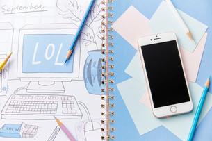 ノートの上に置かれたスマートフォンと色鉛筆のイラスト素材 [FYI02486032]