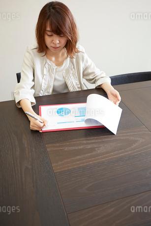 デスクで書類とペンを持つ女性の写真素材 [FYI02487888]