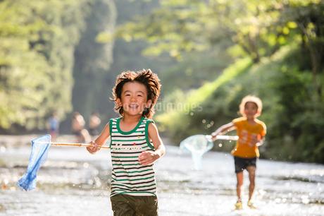 川で網を持って走る子どもの写真素材 [FYI02493397]