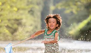 川で網を持って走る子どもの写真素材 [FYI02494041]