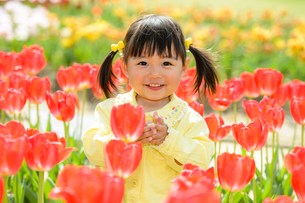 春の公園でチューリップ畑で遊ぶ女の子の写真素材 [FYI02494687]