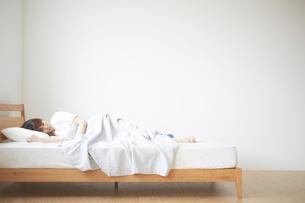 ナチュラルなベッドで眠る女性の写真素材 [FYI02496112]