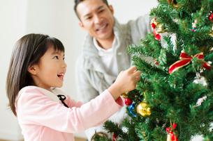 クリスマスツリーに飾り付けをする父と娘の写真素材 [FYI02497562]