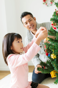 クリスマスツリーに飾り付けをする父と娘の写真素材 [FYI02497878]