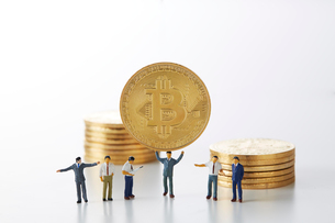 ビットコインを持ち上げるミニチュアのサラリーマンの写真素材 [FYI02499337]