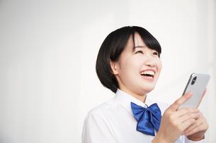 スマートフォンを持つ笑顔な女子高生の写真素材 [FYI02499475]