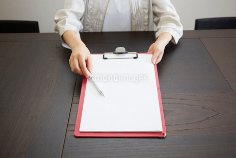 デスクの上でこちらに向けて書類を見せる女性の手元の写真素材 [FYI02502203]