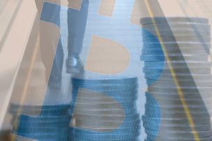 ビジネスマンの足元と積み重ねた硬貨,ビットコインロゴマークの合成の写真素材 [FYI02502681]