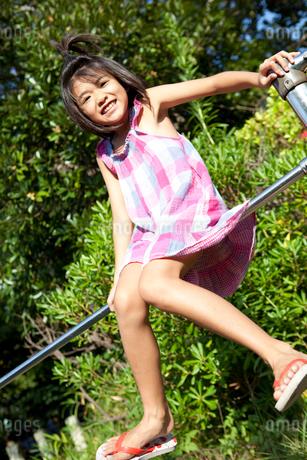 鉄棒で遊ぶ女の子の写真素材 [FYI02502966]