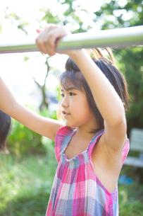 鉄棒で遊ぶ女の子の写真素材 [FYI02503031]