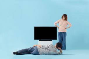テレビの前で寝転がる男性に苛立つ女性の写真素材 [FYI02503034]