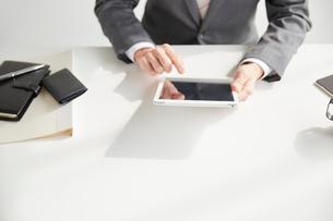 机の前に座ってタブレットを持つサラリーマンの写真素材 [FYI02503365]