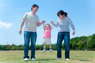 手を繋いで男の子を持ち上げる父と母の写真素材 [FYI02503383]