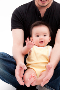父親の組んだ脚に乗る赤ちゃんの写真素材 [FYI02503472]