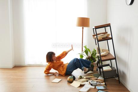 地震で倒れてきた本棚の横で驚く女性の写真素材 [FYI02503497]