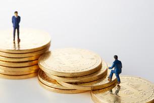 ビットコインの上のミニチュアのサラリーマンの写真素材 [FYI02504205]