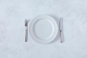白とグレーで塗装された背景と白い皿とカトラリーの写真素材 [FYI02505293]