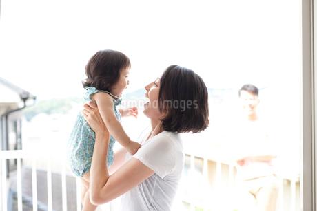 お母さんに抱っこされ笑って喜ぶ赤ちゃんとうしろから見守るお父さんの写真素材 [FYI02505479]