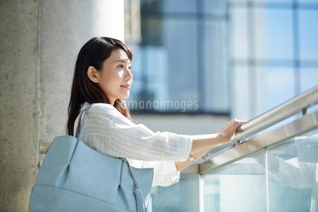 手すりを持って遠くを眺める女性の写真素材 [FYI02505649]