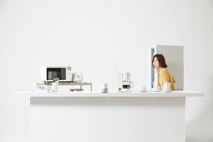 AIスピーカーが置いてあるキッチンで冷蔵庫を開ける女性の写真素材 [FYI02505686]