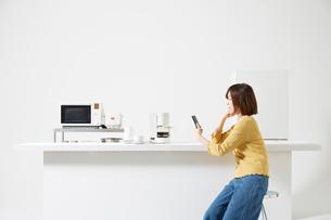 キッチンでスマートフォンを操作する女性の写真素材 [FYI02506236]