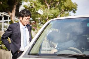 険しい表情の男性と車の窓から顔を出す男性の写真素材 [FYI02506337]