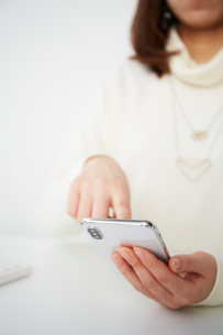 白いテーブルの上でスマートフォンを持つ女性の写真素材 [FYI02507888]