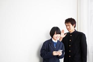 スマートフォンを持った女子高生に話しかける男子高生の写真素材 [FYI02507946]