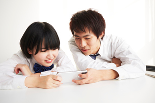 机の上に伏せてスマートフォンを見る男子高生と女子高生の写真素材 [FYI02508502]