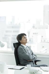 椅子に座り考えるビジネスマンの写真素材 [FYI02508537]