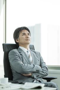 腕を組んで考える表情の日本人ビジネスマンの写真素材 [FYI02508678]