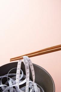 黒い器に入ったメジャーを箸で取る様子の写真素材 [FYI02508748]