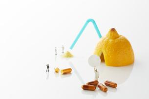 白い天板の上のレモンとビタミン剤とミニチュア人形の写真素材 [FYI02508749]