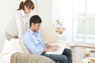 ソファでパソコンをする若い夫婦の写真素材 [FYI02508818]