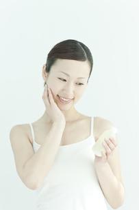 ローションを手に持つ若い女性のスキンケアイメージの写真素材 [FYI02508822]