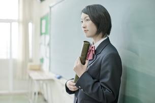黒板の前で卒業証書を持つ女子校生の写真素材 [FYI02508824]